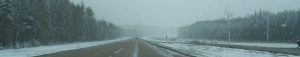 A stretch of highway during a spring snowstorm.