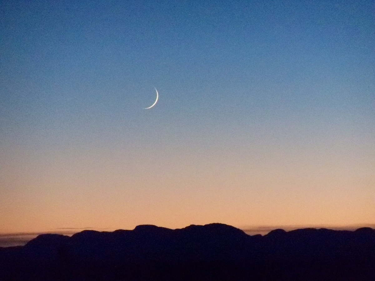 Tiny crescent moon over the Camsell range