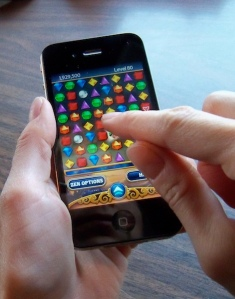hand playing Bejewelled on an iPhone